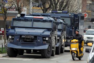 A man rides on a scooter along a street past parked Kosovo police armoured vehicles in southern part of Mitrovica