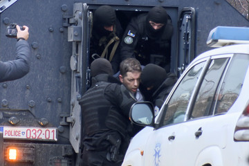 Djuric, head of the Serbian government office on Kosovo, is escorted out of a police vehicle in Pristina
