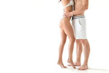 cropped view of young couple in swimwear hugging isolated on white