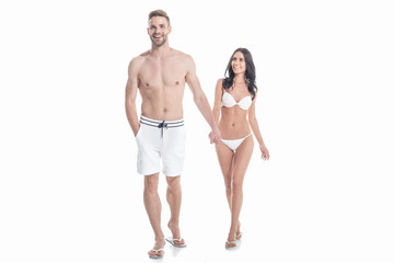 beautiful couple in swimwear holding hands, isolated on white