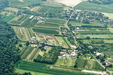 Urban sprawl in the north of Germany with small farmland, roads, houses, commercial enterprises and incoherent woodlands, aerial view