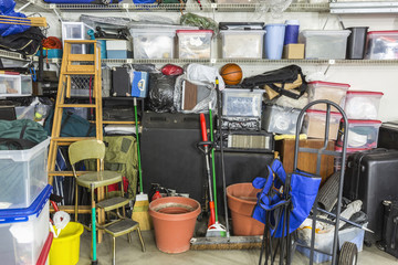 Messy cluttered garage filled with various household storage items.