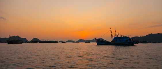 Sunset at Ha Long Bay with rocks on the horizon of landscape and fishing boat near to Cat Ba island in north Vietnam