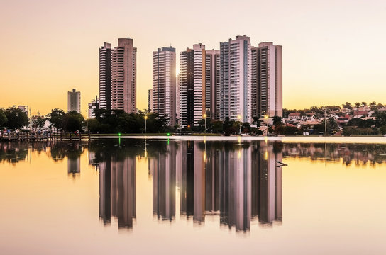 Growing city with few tall buildings reflected on the water of a lake, sunset hour - golden hour. Campo Grande MS, Brasil