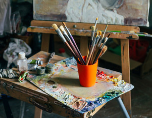 Brushes for drawing on an old wooden easel, stand on the floor