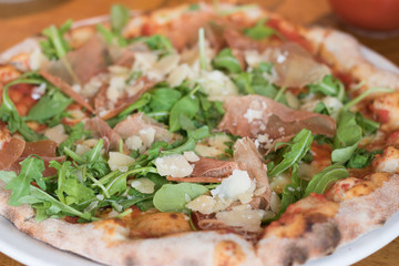 Image of a delicious pizza with ham, cheese and green herb of wild rocket. It is a favorite food of tourists during travel.