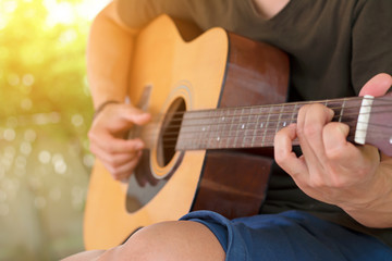 Close up soft focus and blur guitarist's hand is holding the chord EM on acoustic guitar fretboard  in time to relax