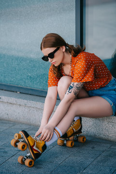 Stylish girl in sunglasses wearing roller skates while sitting on street
