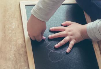 girl drawing on a blackboard detail