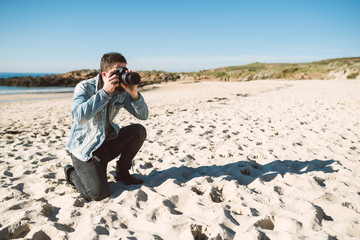 Casual young man taking a picture on the beach