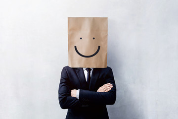 Customer Experience Concept, Portrait of Happy Businessman Client with Smiley Face Emotion on Paper Bag, Crossed arms and wearing Suit, Standing at the Concrete Wall