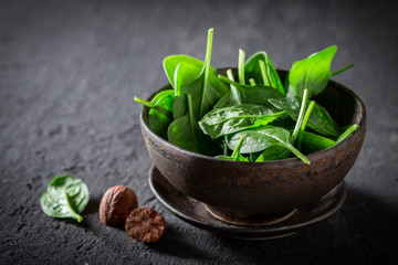 Raw green spinach on gray old stone