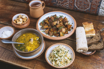 Middle Eastern cuisine dishes in ceramic plates on a wooden table. Soup with mushrooms and herb, pork stew, salad with cabbage and herbs, rusks, bread, lavash, Greek yogurt and compote