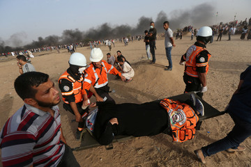 Female demonstrator is evacuated after inhaling tear gas fired by Israeli troops during a protest where Palestinians demand the right to return to their homeland, at the Israel-Gaza border in the southern Gaza Strip