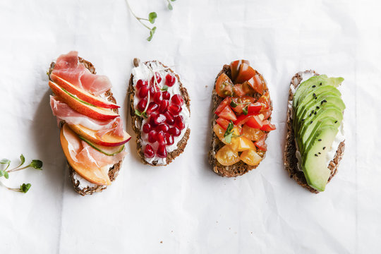Variety of bruschettas with avecado, prosciutto, tomatoes and pomegranate seeds on white background