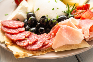Spoed Fotobehang Voorgerecht Piatto con salame, prosciutto, mozzarella di bufala campana e olive nere