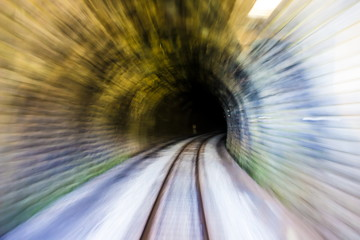 Abstract blurred background, conveying fast train speed along old tunnel railway from light to darkness. Concept speedy blurred motion backdrop