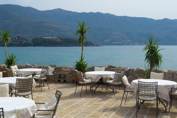 Tables and chairs of a street cafe without people near the sea. Montenegro. Budva
