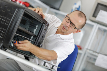 middle-age repairman fixing domestic oven in kitchen