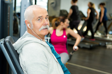 senior man in gym working out with weights squatting