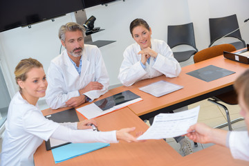 Medical personnel passing papers in a meeting