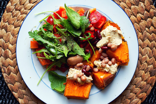 Delicious sweet potato dish with hummus, beans and salad