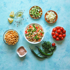 Salad with chickpeas. Set of sliced vegetables and chickpeas on a blue background with copy space.