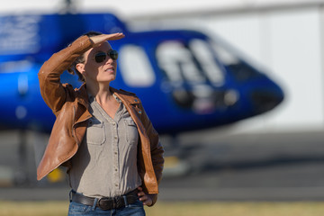 young woman ordering helicopter tour ticket by tablet on airport