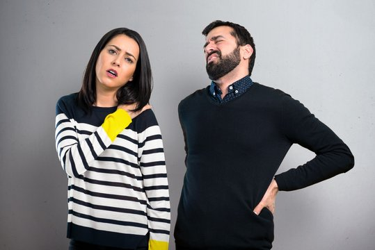 Couple with shoulder pain and back pain on grey background