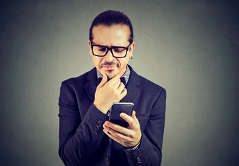 Confused man having problems with smartphone