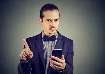 Serious businessman with smartphone showing no attention with finger.