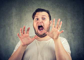Shocked man in panic holding hands up