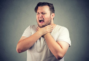 Gasping man holding hands on neck