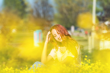 Young girl on a lawn field with yellow flowers