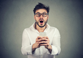 Amazed guy with smartphone looking stunned
