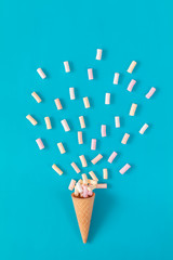 Waffle cone with marshmallow bouquet on blue background