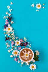 Cup of tea with fresh strawberries, marshmallows and flowers blossom bouquets on blue surface
