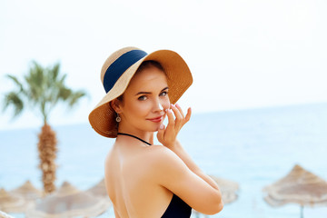 Suntan   woman in hat applying sunscreen solar. Beautiful happy woman smear  lotion  with sun cream   to her nose. Skincare.