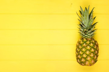 Pineapple on a bright bold yellow wood background. Minimal summer concept. Top view. Copy space.