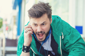 angry young man screaming on mobile phone outdoors
