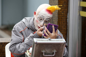 A clown applies makeup to take part in a parade during Peru's Clown Day celebrations in Lima
