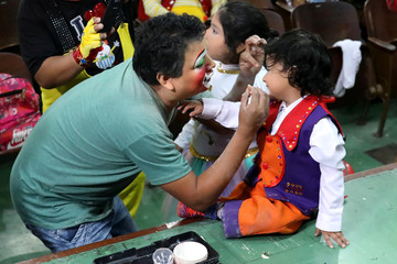 Freddy Flores applies makeup on his son's face before they take part in a parade during Peru's Clown Day celebrations in Lima