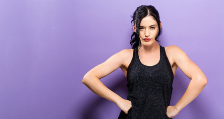 Powerful young fit woman posing on a solid purple background
