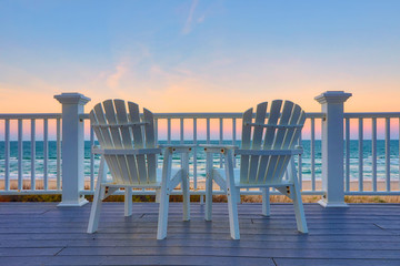 Adirondack Chair sits on the balcony deck of a house looking out over the beach and the ocean