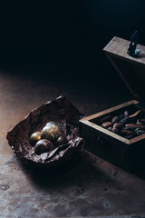 closeup view of wooden box with nuts and chocolate candies on crumpled paper