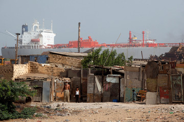 A labourer and his son stand outside their makeshift home, with a ship in the background that is to be dismantled for scrap metal at ship-breaking yard in Gadani, Baluchistan province