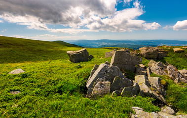 boulders on top of Runa mountain. beautiful landscape with distant peak under the cloud on a blue sky