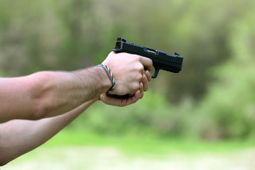 Man hands shooting with black handgun