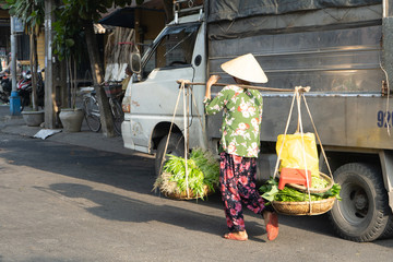 Old woman goes to the local market. Street seller in Hoi an, Vietnam.