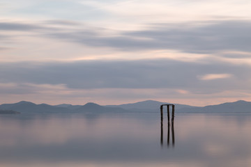 A  minimalistic view of a lake at sunset, with soft light and to